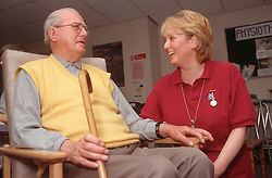 Elderly man sitting in chair holding walking stick talking with female nursing assistant,
