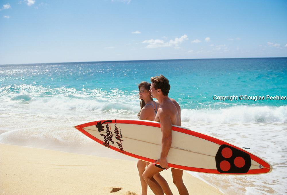 Couple walking on beach with surfboard, Hawaii