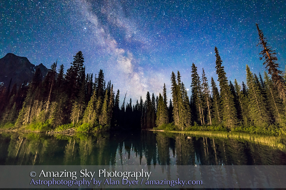 The Milky Way over the side pond at Emerald Lake, Yoho National Park, BC., from the bridge to the Lodge. Lights from the Lodge illuminate the trees. Perpetual twilight near solstice (I shot this JUne 6, 2016) lights the sky deep blue. Saturn is the bright object in haze shining through the trees at right. <br /> <br /> This is a stack of 8 x 25-second exposures for the foreground (mean combined to smooth noise), and one untracked exposure for the sky (to minimize trailing), all at f/2.8 with the Rokinon 14mm lens and Canon 6D at ISO 6400. Unfortunately, I should have framed the scene a bit more to the left to take in more of Cathedral Mountain. Oh well! It was at the end of a long night!