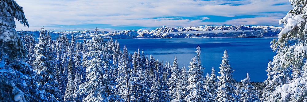 A panorama photo of Lake Tahoe on a winter morning after a snowstorm. Looking west across the lake is the view of Mount Tallac and the west shore.