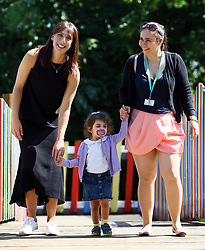 Samantha Cameron walks with 2 year old Julieta Vieira and her mother Andreia (right) after hosting a coffee morning to celebrate the work of charity KIDS and the services that they deliver to disabled children, young people and their families, at Hackney Adventure Playground in London.