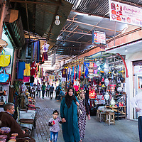 People walking through the crowded market stalls in the Medina of Marrakesh, Morocco.