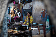 Bajau mother and her daughter cooking their dinner on Mabul Island