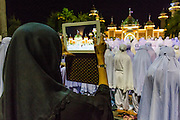 11 JULY 2013 - PATTANI, PATTANI, THAILAND:  A woman photographs Ramadan services at Pattani Central Mosque in Pattani, Thailand, with her iPad. The mosque is one of the busiest in south Thailand. About 15,000 people attend nightly Ramadan services in the mosque. Ramadan is the ninth month of the Islamic calendar, and the month in which Muslims believe the Quran was revealed. Muslims believe that the Quran was sent down during this month, thus being prepared for gradual revelation by Jibraeel (Gabriel) to the Prophet Muhammad. The month is spent by Muslims fasting during the daylight hours from dawn to sunset. Fasting during the month of Ramadan is one of the Five Pillars of Islam.     PHOTO BY JACK KURTZ