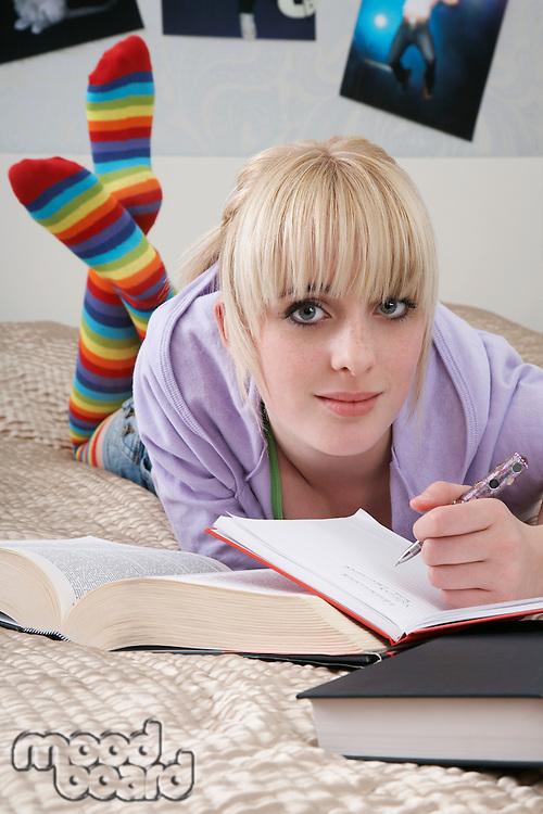Portrait of teenage girl (16-17) doing homework on bed