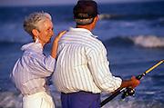 Senior couple surf fishing  at the beach