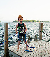 Matthew Herrmann helps tie up the family boat at Camp Island on Lake Winnipesaukee.  Karen Bobotas for the Laconia Daily Sun