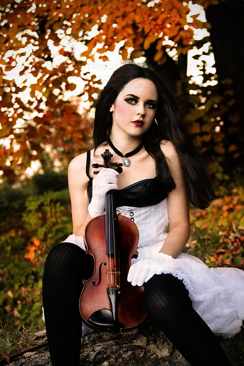 A pretty girl with long black hair and pale skin sitting in an autumnal setting and holding a violin, looking at the camera.