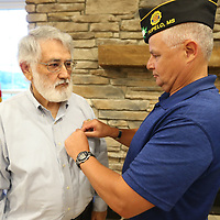 Kenneth Patterson gets his National Defense Service Medal pinned by American Legion Post 49 Commander Mike Pettigrew Thursday night.