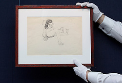 "© Licensed to London News Pictures. 21/03/2014. London, UK. A member of Sotheby's auction house staff adjusts 'untitled illustration of a hairy woman holding a miniature man by the arm' (GB£12,000-15,000) by the late Beetles singer John Lennon, allegedly the piece that brought him to the attention of his future wife Yoko Ono, during the press view for a new sale at Sotheby's auction house in London today (21/03/2014). The auction, entitled ""You Might Well Arsk"", features original drawings and manuscripts by the singer from 1964-1965. Photo credit: Matt Cetti-Roberts/LNP"