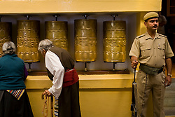 Tibetan buddhists pass by prayer wheels as an Indian security guard keeps watch during a morning prayer ceremony with Dalai Lama in Dharamsala, India, May 26, 2009.