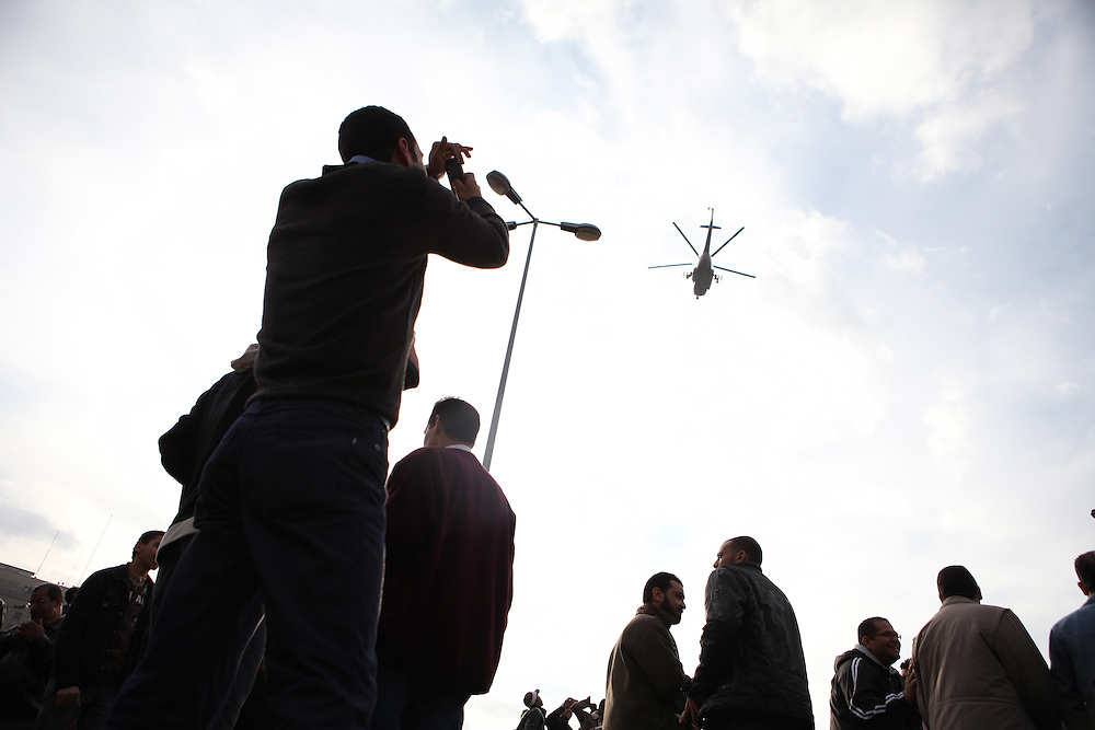 Protesters at Cairo's main Tahrir (Liberation) Square watch as an Egyptian army helicopter flies overhead.
