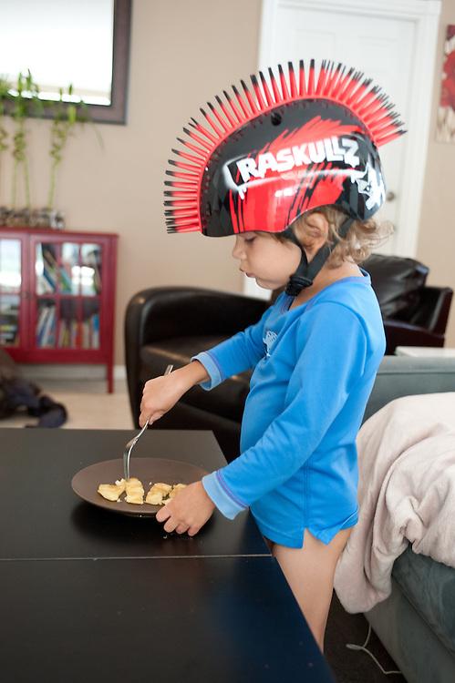 young boy wearing Raskullz Mohawk helmet, eating pancake while standing up. blue shirt, no pants