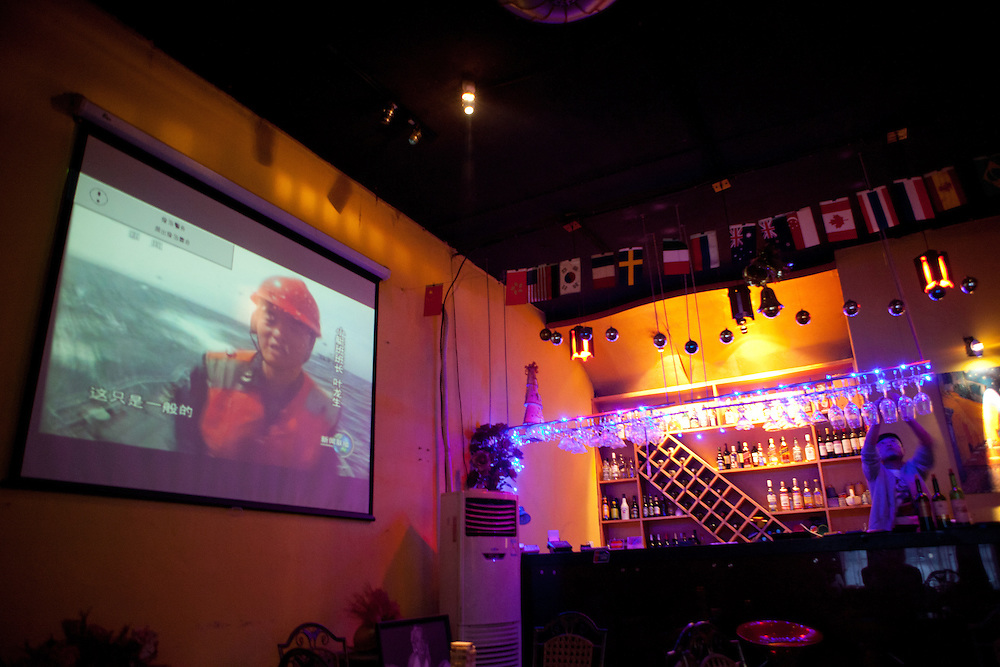 """News projection at """"Beijing Bar"""" in the center of Beijing. Beijing is the capital of the People's Republic of China and one of the most populous cities in the world with a population of 19,612,368 as of 2010."""