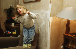 Young girl standing on chair preparing to jump,