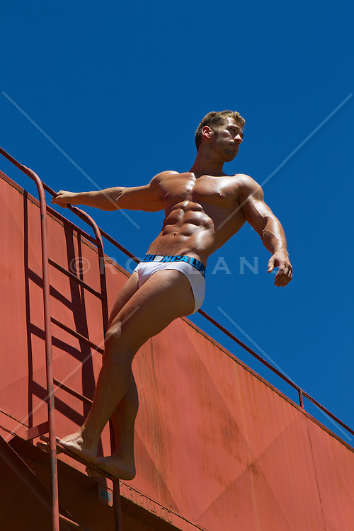 muscular man in briefs on a ladder against the sky in New Mexico