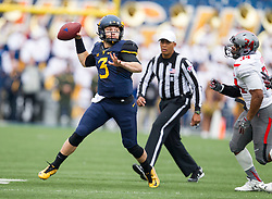 Nov 7, 2015; Morgantown, WV, USA; West Virginia Mountaineers quarterback Skyler Howard rolls out of the pocket to pass during the second quarter against the Texas Tech Red Raiders at Milan Puskar Stadium. Mandatory Credit: Ben Queen-USA TODAY Sports