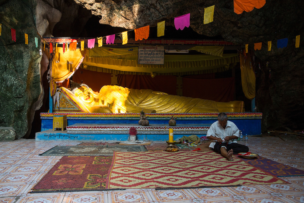 A golden reclining Buddha statue in the sunlight in a Killing Cave of Phnom Sampeau in Battambang region, Cambodia, South East Asia. The lying Buddha represents his last illness, about to enter the parinirvana (after death). Many victims were killed and thrown into these caves during the Khmer Rouge in 1970s. A Cambodian man sits in front of the statue making wrist band souvenirs.  (photo by Andrew Aitchison / In pictures via Getty Images)