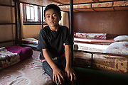 A young Nepalese orphan sits on his bed in his bedroom in the Voice of Children rehabilitation center in Kathmandu, Nepal. The not-for-profit organisation supports street children and those who are at risk of sexual abuse through educational and vocational training opportunities, health services and psychosocial counseling. This boy also lives in the center while he is part of the rehabilitation program and hopes to be fostered.