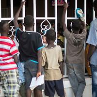 02/03/2014. Bissau. Guinée Bissau. Une petite fille mange une glace à la terrasse d'un café de la place Imperio pendant qu'autour d'autres enfants font la quête. ©Sylvain Cherkaoui pour JA.