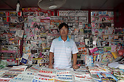 A magazine seller in his stall, surrounded by magazines, and newspapers in Shanghai.