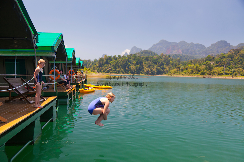 Ranforest Camp Elephant Hills Luxury Floating Tented Camp in the rainforest in Southern Thailand.  Tourist kids jumping off of their luxury tent deck into the lake.