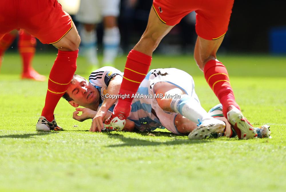 Lionel Messi of Argentina gets tangled up in the legs of Marouane Fellaini of Belgium