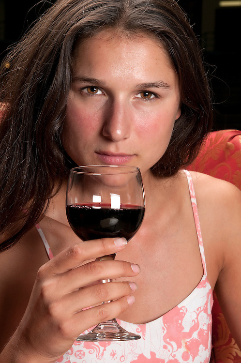 Young brunette enjoys a glass of wine in a restaurant.