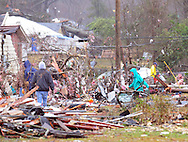 Residents sort through scattered belongings on Tuesday in Petal as Pine Belt residents begin to clean up from the EF4 tornado which swept through the area Sunday.