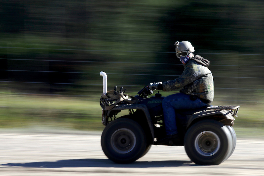 A man races by on a four-wheeler at the Redneck Yacht Club in Punta Gorda, Fla. Photo by: Greg Kahn