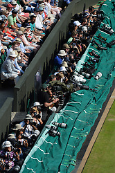 © London News Pictures. 07/07/2013 . London, UK. Photographers watch Andy Murray in action during the men's singles final against Novak Djokovic of Serbia at the Wimbledon Lawn Tennis Championships final. Andy Murray won the match  becoming the first British male to win the tournament in 77 years. Photo credit: Mike King/LNP