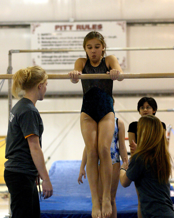 Hannah Billstone (L) and Emily Storms(R) help Christine Kuzminski on the uneven bars at the Lakewood Y 12.4 photo by Mark L. Anderson
