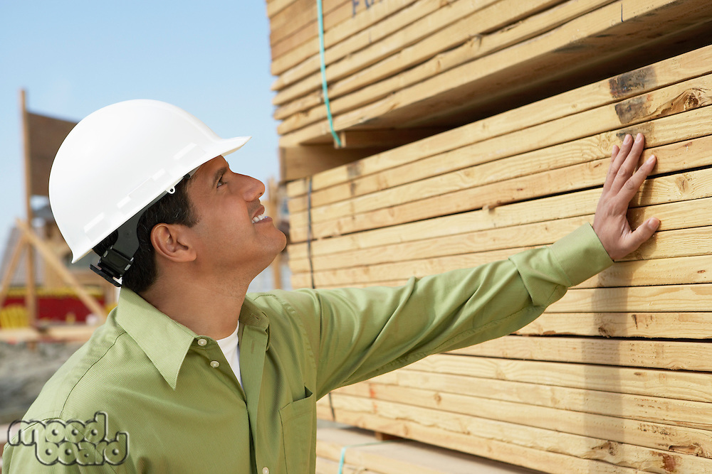 Construction Worker in hard hat inspecting Lumber on job site side view