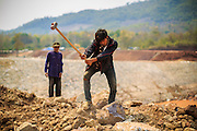15 MARCH 2013 - ALONG HIGHWAY 13, LAOS:  Laborers work on a construction site for a series of reservoirs and dams along Highway 13 north of Luang Prabang, Laos. The paving of Highway 13 from Vientiane to near the Chinese border has changed the way of life in rural Laos. Villagers near Luang Prabang used to have to take unreliable boats that took three hours round trip to get from the homes to the tourist center of Luang Prabang, now they take a 40 minute round trip bus ride. North of Luang Prabang, paving the highway has been an opportunity for China to use Laos as a transshipping point. Chinese merchandise now goes through Laos to Thailand where it's put on Thai trains and taken to the deep water port east of Bangkok. The Chinese have also expanded their economic empire into Laos. Chinese hotels and businesses are common in northern Laos and in some cities, like Oudomxay, are now up to 40% percent. As the roads are paved, more people move away from their traditional homes in the mountains of Laos and crowd the side of the road living off tourists' and truck drivers.   PHOTO BY JACK KURTZ