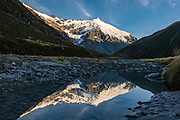 The Dart River reflects glacier-clad Mt Edward (2620m) on a spectacular day hike from Dart Hut to Cascade Saddle, in Mount Aspiring National Park, Otago region, South Island of New Zealand.