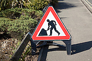 Man at work red triangular road sign