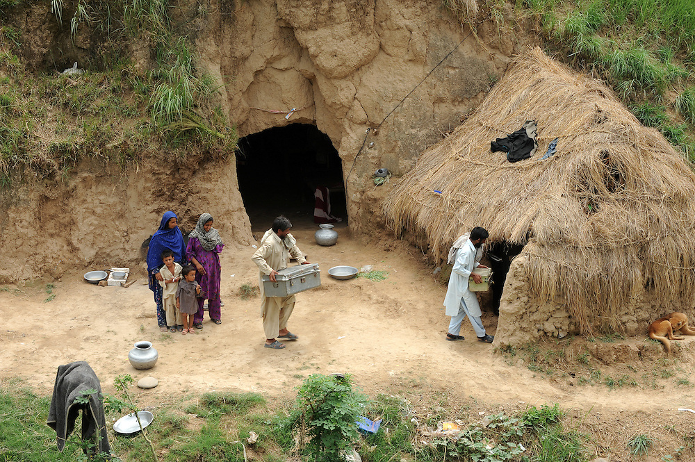 11/8/2009 Displaced people from Swat Bakhat Nazeera and Namro Gul with children Parwari  and Meer look on as their husbands Chura and Mian carry their luggage into the cave in Haripur where they are staying until it is safe to return home. PHOTO KIM HAUGHTON