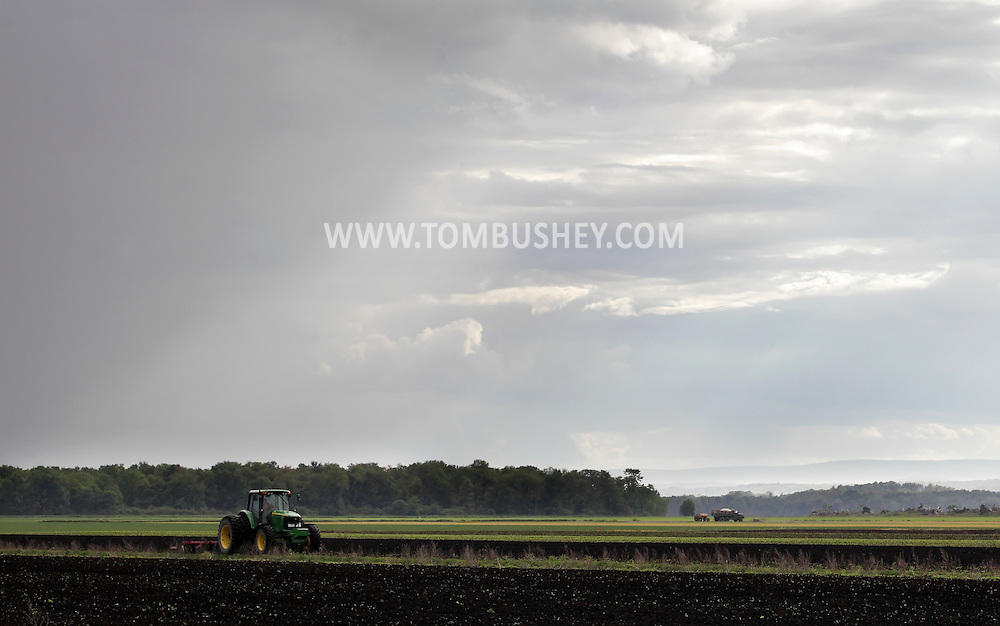 Goshen, New York - A farmer in a tractor plows a field  in the Black Dirt region under changing skies on May 21, 2011.