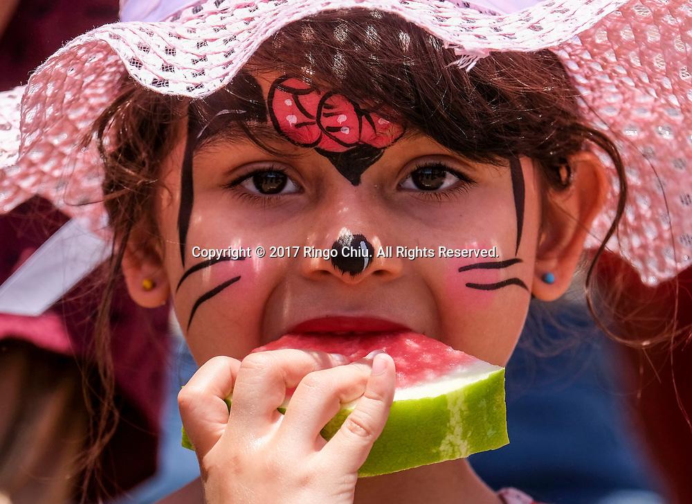 新华社照片,洛杉矶,2017年7月30日<br />     (国际)(1)第五十五届加州西瓜节<br />     7月29日,小孩子品尝鲜甜西瓜。<br />     在美国洛杉矶,大批民众出席了&quot;第五十五届加州西瓜节&quot;。<br />     新华社发(赵汉荣摄)<br /> A girl with face painted enjoys the watermelon at the 55th Annual California Watermelon Festival in Los Angeles, the United States, Saturday, July 29, 2017. (Xinhua/Zhao Hanrong)