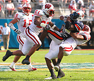 Auburn running back Kenny Irons (23) is brought down by Wisconsin's Levonne Rowan (21) and LaMarr Watkins, right, as teammate Joe Stellmacher (16) watches during the second half of the Capital One Bowl football game in Orlando, Florida.
