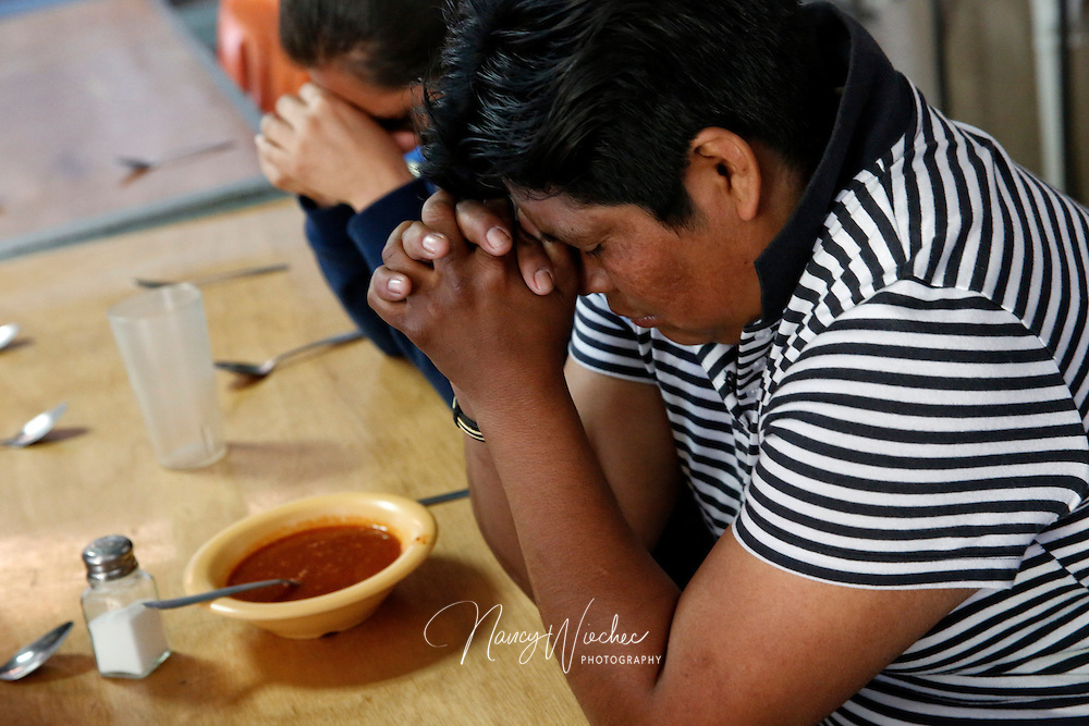 Women pray before eating dinner at the Aid Center for Deported Migrants in Nogales, Sonora, March 31. Dinner that evening was served by visiting U.S. bishops, including Auxiliary Bishop Luis Zarama of Atlanta, pictured at far left. The center, run by the Kino Border Initiative, was one stop the bishops made during their tour of the border area near Nogales. (CNS photo/Nancy Wiechec) (April 1, 2014)