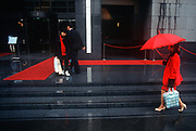 While still a British colony, a red 1990s theme of carpet, rope barrier, umbrella and clothing outside the Bank of China, on 21st April 1995, in Central, Hong Kong, China. (Photo by Richard Baker / In Pictures via Getty Images)