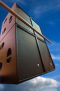 A Large bank of Loudspeakers floating in a blue sky