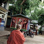 "May 14, 2013 - Mandalay, Myanmar: Ashin Wirathu, the buddhist monk leader of Burma's anti-Muslim movement 969 group, walks by posters of opposition leader Aung San Suu Kyi, in the grounds of Mosayein Monastery in central Mandalay. Wirathu, who was jailed in 2003 for inciting religious hatred, refers to himself as ""the Burmese Bin Laden"". (Paulo Nunes dos Santos/Polaris)"