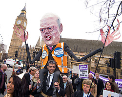 © Licensed to London News Pictures. 07/03/2014. Westminster, London, UK. Protestors with an effigy of Justice Secretary Chris Grayling march onto Parliament Square as part of the Save UK Justice campaign against legal aid cuts. Photo credit : David Tett/LNP