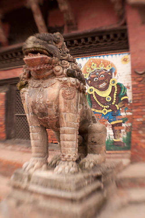 A lion statue a mural of demon guard a temple in Patan's Durbar Square.
