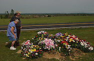 Rainsville, Alabama: Gene and Ann Watkins pay respects to their cousins, husband and wife Hubert Wooten, 72,  and Juanita Wooten, 70, who were killed in tornados that ripped through this rural northeastern Alabama town. The Wootens' daughter, Izell, was also killed, and is buried a few plots away. Officials confirmed that at least 33 people were killed in Rainsville and surrounding DeKalb County.  (PHOTO: MIGUEL JUAREZ LUGO)