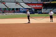 ANAHEIM, CA - AUGUST 12:  The grounds crew waters the infield before the Seattle Mariners game against the Los Angeles Angels of Anaheim on Sunday, August 12, 2012 at Angel Stadium in Anaheim, California. The Mariners won the game 4-1. (Photo by Paul Spinelli/MLB Photos via Getty Images)