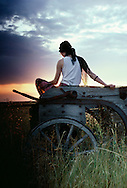 Woman sits on old wagon watching sunset, South Dakota, <br /> MODEL RELEASED