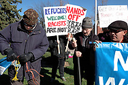CANADA, Windsor. 07 April 2017. Windsor Peace Coalition holds a demonstration against yesterday's United States bombing of a Syrian air force base. About twenty people, mostly older, gather at Jackson Park during the afternoon rush hour. There is also a counter demonstration by two men holding a Trump banner on the same street corner. NOTE: Agefotostock exclusive image, G99-2864930, to license go to http://www.agefotostock.com/age/en/Stock-Images/Rights-Managed/G99-2864930